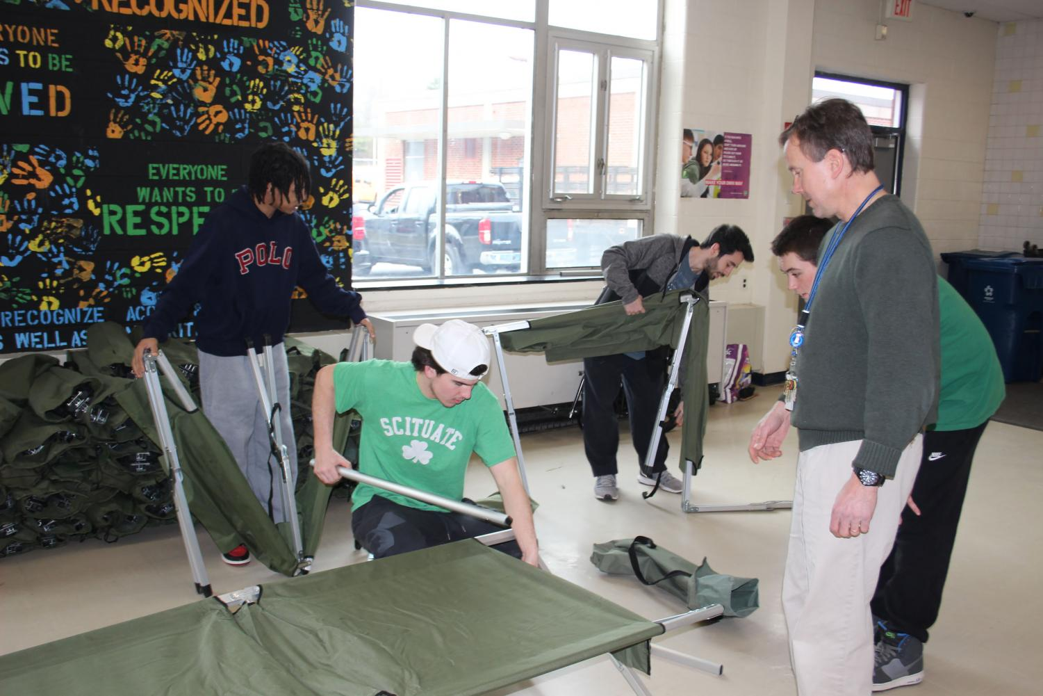 Students and SHS teacher Brad Mingles start to set up the community storm shelter in the SHS cafeteria. Photo Courtesy of Lauren Montgomery
