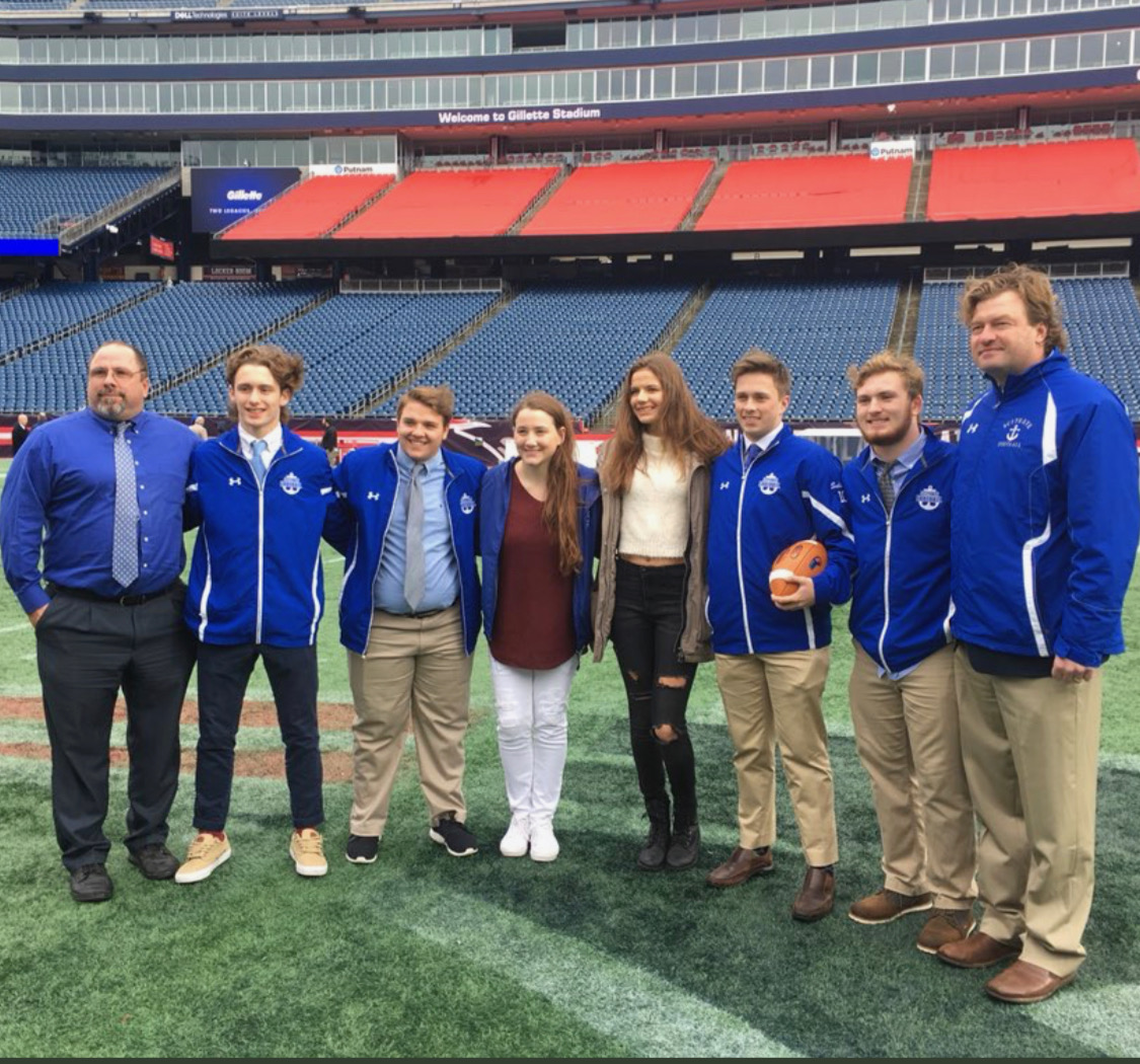 On the field. From left, Vice Principal Bill Luette, Captain Daniel May, Captain Josh Comeau, Cheer Captain Hannah Jordan, Cheer Captain Julia Babb, Captain Aidan Sullivan, Captain Josh McKeever, and Head Coach Herb Devine